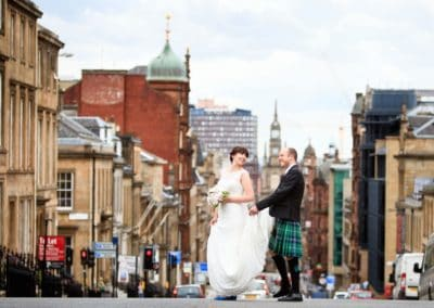 a wedding couple cross the road on their wedding day in glasgow
