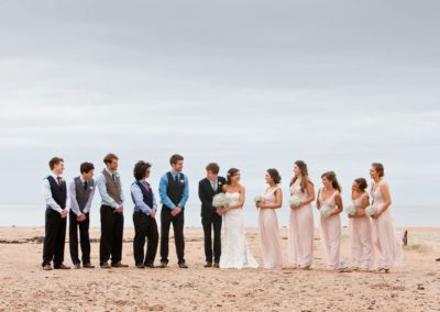 a bridal party on the beach at harvest moon weddings
