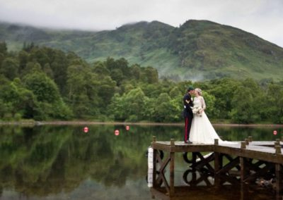 a couple are reflected off the loch in a romantic scottish wedding