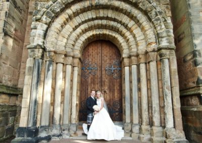 a couple stand on the steps of dunfermline abbey on their wedding day
