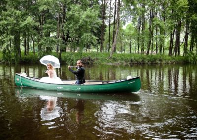 a wedding couple take a kayak down the river on their wedding day