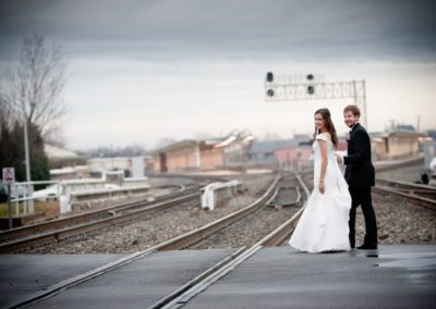 a couple cross the railroad tracks on their wedding day in greensboro