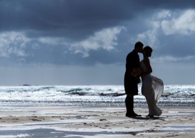 a couple are silhouetted against the sea on their wedding day on the isle of lewis