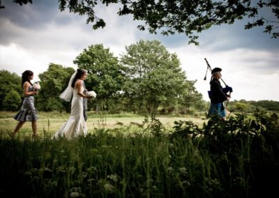 a bride walks down to her wedding, being led by a bagpiper