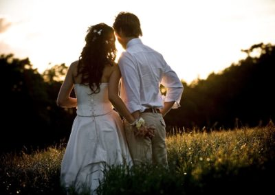 a couple stand in a field during sunset on their wedding day
