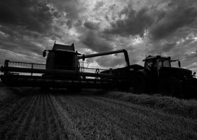 A combine harvester emptying his load into a tractor and trailer.