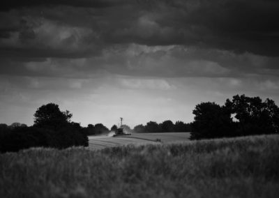 A long distance black and white photograph of a combine harvester in a field.