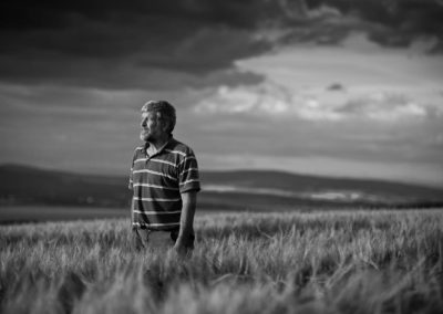 a black and white photograph of a farmer in a field at dusk taken by inverness commercial photographer, roddy mackay