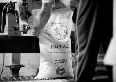 A workman seals another bag of malt on a bagging line.