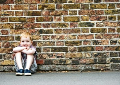 a young boy is photographed against a brick wall in greenwich, london