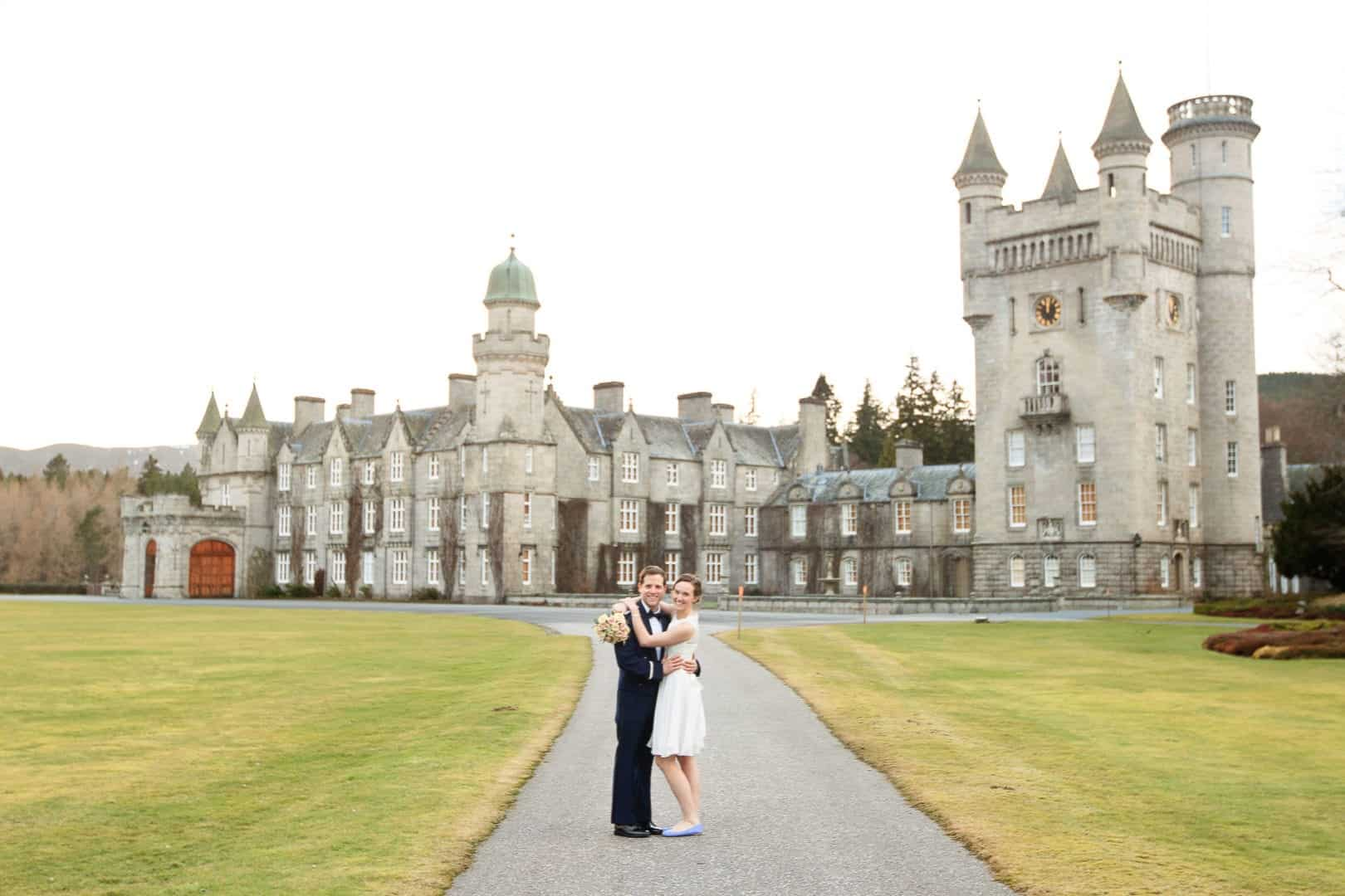 a bride and groom standing outside balmoral castle in aberdeenshire