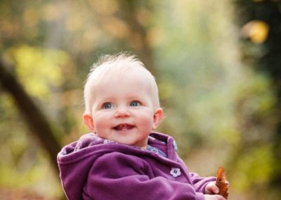 a young child smiles for the camera during her family portrait session