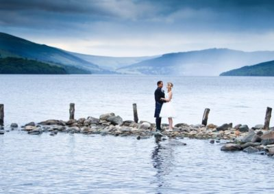 a bride and groom share a hug on the banks of loch tay