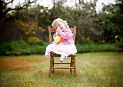 a young child sits on a chair in her garden