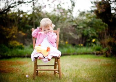 a young child sucks her thumb sitting on a chair in her garden