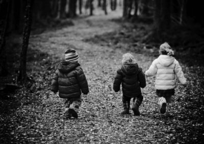 young children walk through the woods on the outskirt of inverness