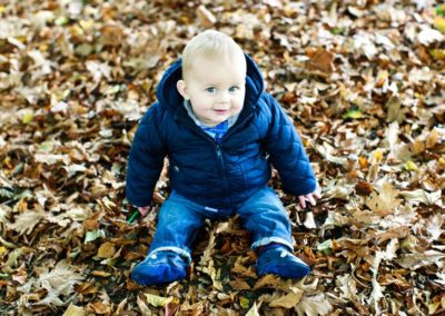 a younf boy sits in leaves in the park