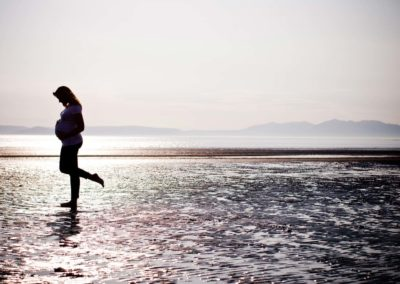 a pregnant mother is silhouetted against the sun on a maternity session on troon beach
