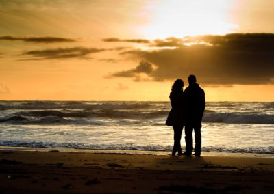 a couple look out at the sunset on their engagement photography session in eorpie, ness