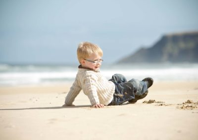 a young boy runs around in his family portrait session in lewis