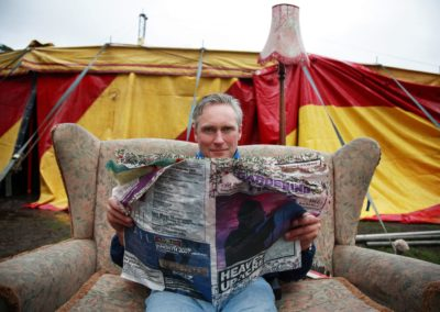 joe gibbs of belladrum festival sits on a couch outdoors at the music festival