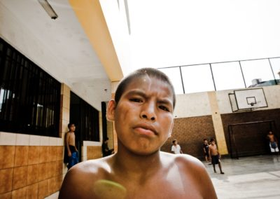 a young boy who lives on the streets of lima poses for the camera
