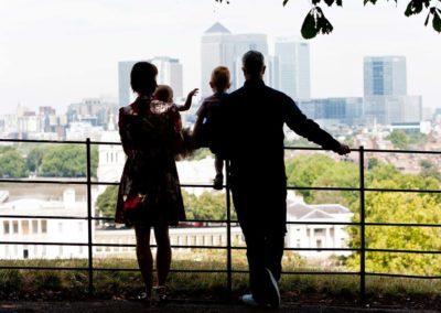 a family look out over london from the viewpoint at greenwich park