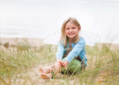 a young girl looks at the camera on a beach in morayshire