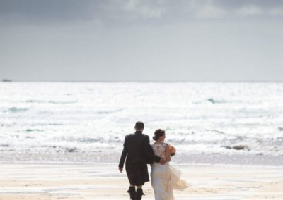 a bride and groom walk on a beach in lewis on their wedding day