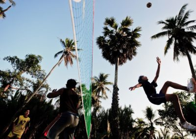a young man stretches to make an overhead kick in a game of sepak takraw in malaysia