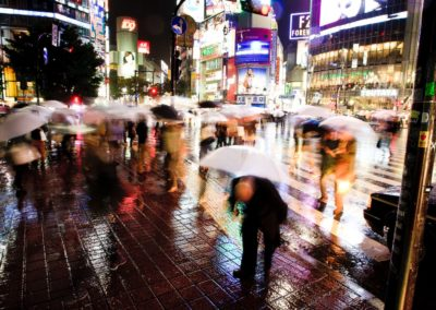 people are blurred as they walk past the camer a in shibuya, tokyo