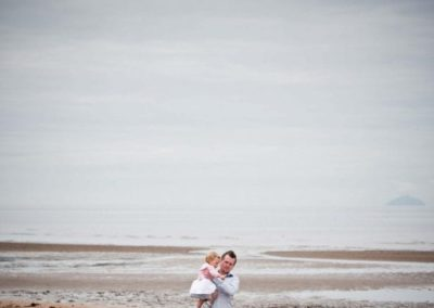 a father and daughter in their family portrait session on troon beach