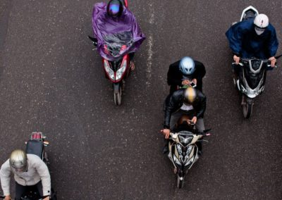 motorcyclists look at their mobile phones while riding through the streets of hanoi