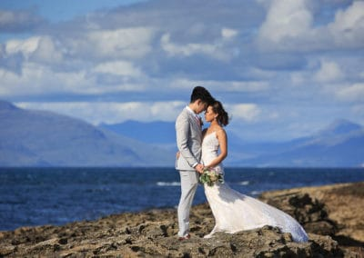 An asian bride and groom pose for their pre wedding photo shoot on a beach in scotland