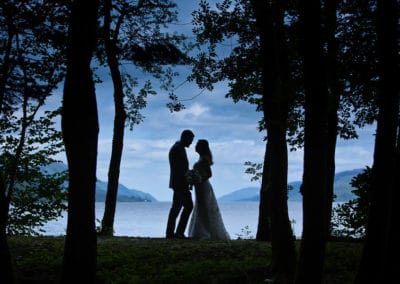 a bride and groom are silhouetted against the sky by loch ness on a pre wedding photo session in scotland